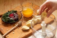 el cocinar, zumo de naranja, plátano, zarzamoras congeladas de las fresas e ingredientes y licuadora vivos, juicer, tulipanes del Fotos de archivo