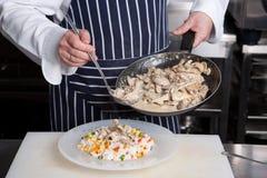 El cocinero añade la carne al risotto Fotos de archivo libres de regalías
