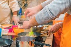 El cocinero añade la pimienta a la carne en cocinar el taller fotografía de archivo