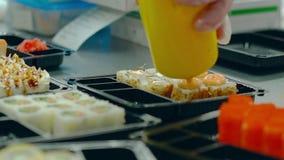 El cocinero añade la salsa a los rollos japoneses con la anguila asada almacen de video