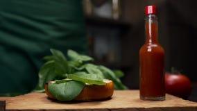 El cocinero añade las hojas de la espinaca a la hamburguesa con las verduras y de los verdes, bollos y hamburguesas, haciendo de  almacen de video