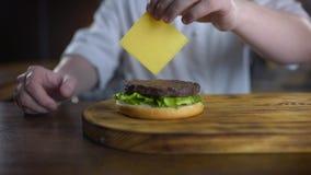 El cocinero añade el queso cheddar cortado a la hamburguesa y lo pone sobre la chuleta, cocinando las hamburguesas en la cámara l almacen de metraje de vídeo