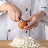 El cocinero añade un huevo fotos de archivo libres de regalías
