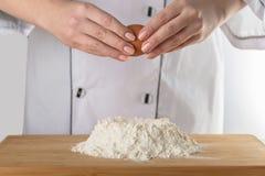 El cocinero añade un huevo imagenes de archivo