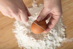 El cocinero añade un huevo imagen de archivo libre de regalías