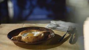 El cocinero añade un pedazo de mantequilla al khachapuri cocinado, servido en la mesa de comedor metrajes