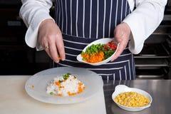 El cocinero añade verduras al risotto Imagen de archivo