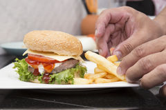El cocinero adornó la hamburguesa y a los franceses Freid Imagenes de archivo