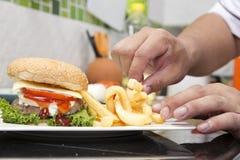 El cocinero adornó la hamburguesa y a los franceses Freid Imagen de archivo