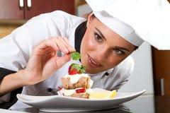 El cocinero adorna el plato imagen de archivo