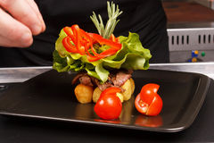 El cocinero adorna el plato sabroso Imágenes de archivo libres de regalías
