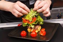 El cocinero adorna el plato sabroso Foto de archivo libre de regalías
