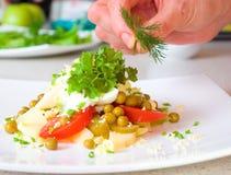 El cocinero adorna la ensalada Fotos de archivo