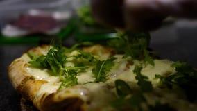 El cocinero adorna la pizza con verdes Cap?tulo El primer del cocinero pone la ensalada del arugula que echa en la pizza acabada  almacen de metraje de vídeo
