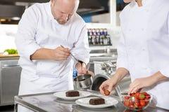 El cocinero adorna la torta del postre con la salsa de chocolate en cocina Imagenes de archivo