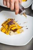 El cocinero adorna un plato Imagen de archivo libre de regalías
