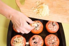 El cocinero agrega el queso al tomate relleno foto de archivo libre de regalías