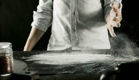 El cocinero amasa la pasta con la harina en la tabla de cocina para el movimiento fotos de archivo