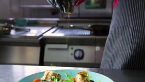 El cocinero asperja el plato acabado con la salsa de los salmones y de la espinaca almacen de video
