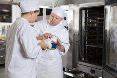 El cocinero ayuda al estudiante con cocinar en una cocina grande Imágenes de archivo libres de regalías