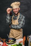 El cocinero barbudo del cocinero sostiene la berenjena Foto de archivo