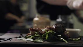 El cocinero borroso sirve la carne cocida lista con verdes