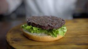 El cocinero cocina la hamburguesa y pone la chuleta a las hojas de la ensalada verde fresca, restaurante de los alimentos de prep almacen de metraje de vídeo