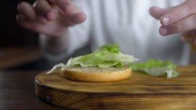 El cocinero cocina la hamburguesa y pone las hojas de la ensalada verde fresca al bollo, haciendo las hamburguesas en el restaura almacen de video