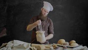 El cocinero comprueba la calidad de la harina, colocándose cerca de una tabla adornada con los pasteles de su panadería almacen de video