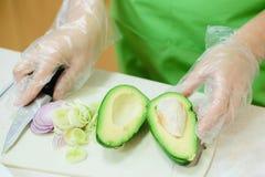 El cocinero corta el aguacate para la ensalada imagen de archivo