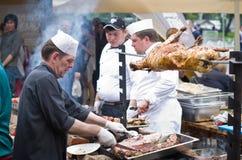 El cocinero corta la carne, carne en un escupitajo Imagenes de archivo