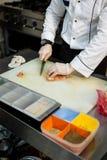 El cocinero corta la carne en el tablero blanco al lado de la caja con las especias en el surtido foto de archivo