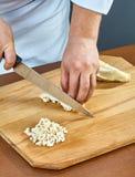 El cocinero corta la carne hervida del pollo para preparar una colección completa gelatinada de recetas culinarias Imagen de archivo libre de regalías