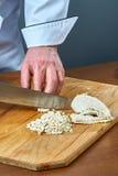 El cocinero corta la carne hervida del pollo para preparar una colección completa gelatinada de recetas culinarias Imágenes de archivo libres de regalías