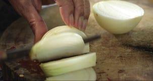El cocinero corta la cebolla El cortar de la cebolla Medios anillos de cebollas Las manos del cocinero Verduras cortadas para la  almacen de metraje de vídeo