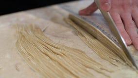 El cocinero corta la pasta para las pastas Foco selectivo almacen de video