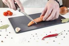 El cocinero corta la zanahoria en tabla de cortar negra imagen de archivo
