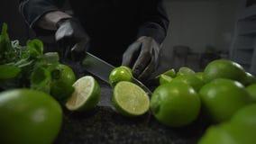 El cocinero corta las cales maduras por el cuchillo afilado grande en la tabla de cocina oscura de la roca, haciendo de mojito, l almacen de video
