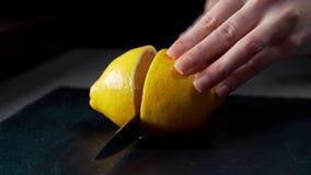 El cocinero corta el limón por la mitad, ensalada de fruta, muchacha prepara las bebidas frescas, limón para el tequila, frutas e almacen de metraje de vídeo