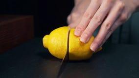 El cocinero corta el limón por la mitad, ensalada de fruta, muchacha prepara las bebidas frescas, limón para el tequila, frutas e metrajes