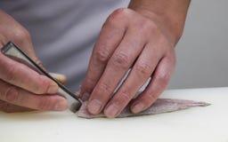 El cocinero corta los pescados en pedazos de sushi Foto de archivo