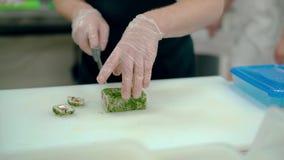 El cocinero corta los rollos japoneses con eneldo almacen de metraje de vídeo