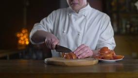 El cocinero corta los tomates rojos frescos en el tablero de madera en una barra en la cámara lenta, cocinando la ensalada vgeta almacen de video