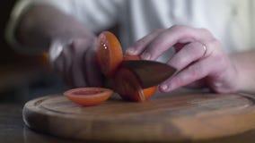 El cocinero corta los tomates rojos frescos en el tablero de madera en una barra en la cámara lenta, cocinando la ensalada vgeta metrajes
