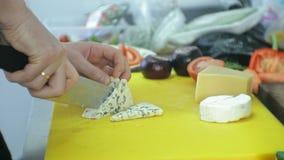 El cocinero corta el queso en la cocina del restaurante metrajes