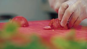 El cocinero corta un tomate fresco para una ensalada con un cuchillo almacen de video