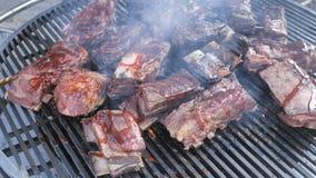 El cocinero da vuelta a la carne en la parrilla con las llamas del fuego Parrilla americana, friendo la carne fresca, barbacoa de almacen de metraje de vídeo