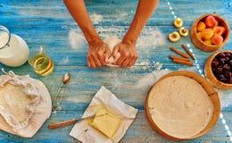 El cocinero de la chica joven amasa y rodando la pasta con el perno Imagen de archivo libre de regalías
