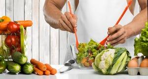 El cocinero de la mano del hombre hace las verduras de la mezcla la ensalada en cocina fotografía de archivo