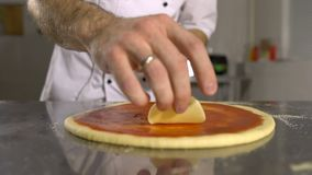 El cocinero de la mano pone el queso en base de la pizza en el primer de la salsa de tomate almacen de video